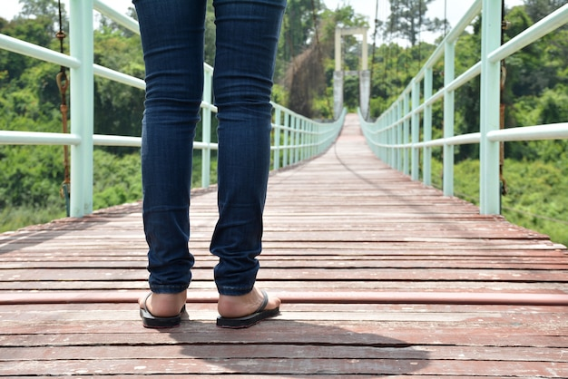 Gambe di un uomo donna in piedi su un ponte sospeso