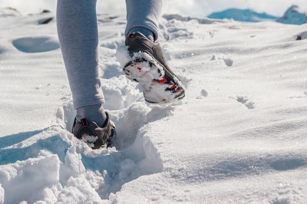 Le gambe di una donna in scarpe invernali sportive nella neve profonda.