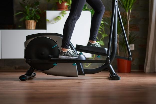 Gambe di donna che si allenano su bici ellittica nel soggiorno di casa