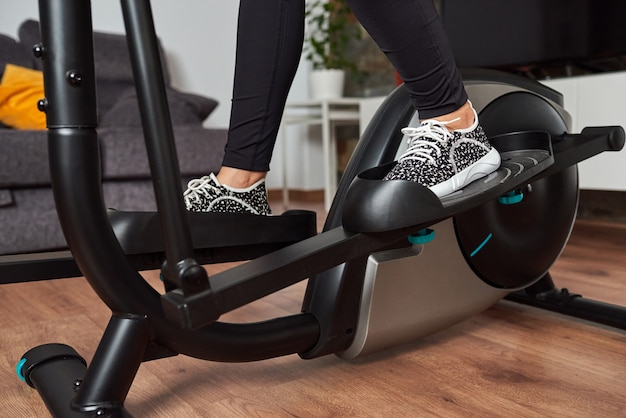 Gambe di donna che si allenano su cross trainer ellittico nel soggiorno di casa