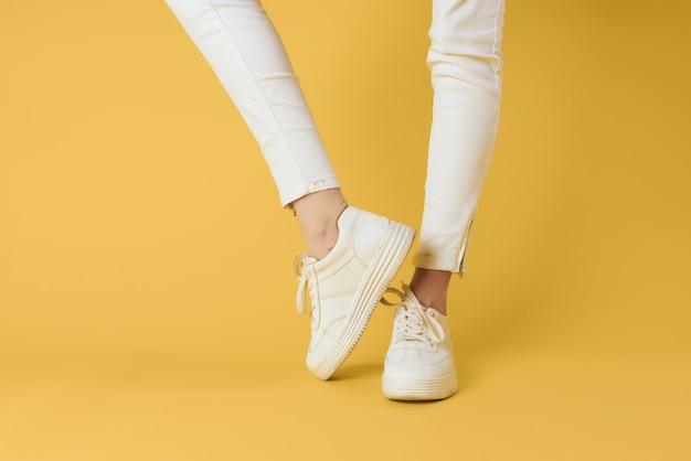 Gambe di donna in pantaloni bianchi e scarpe da ginnastica