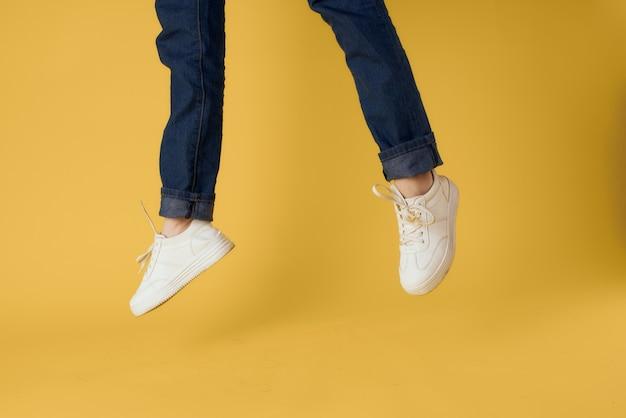 Gambe di donna in scarpe da ginnastica bianche