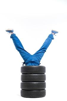 Le gambe dell'operaio sporgono dal mucchio di pneumatici