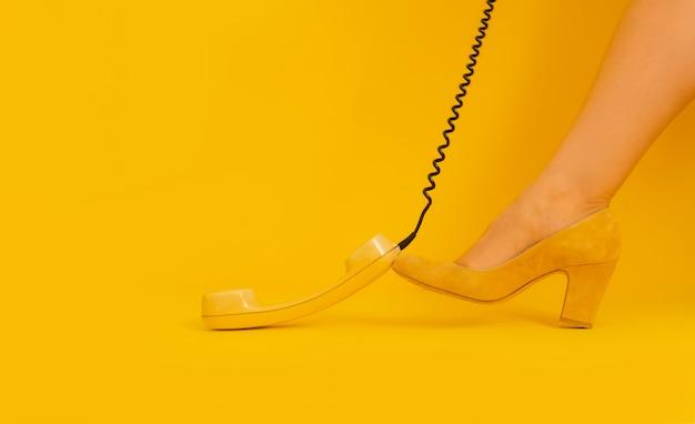 Gambe sfondo giallo retro ricevitore ricevitore tubo scarpe lady vintage telefono anni '80 e '90