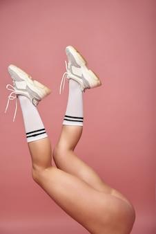 Gambe di una giovane donna caucasica in calzini lunghi e scarpe da ginnastica su una parete rosa