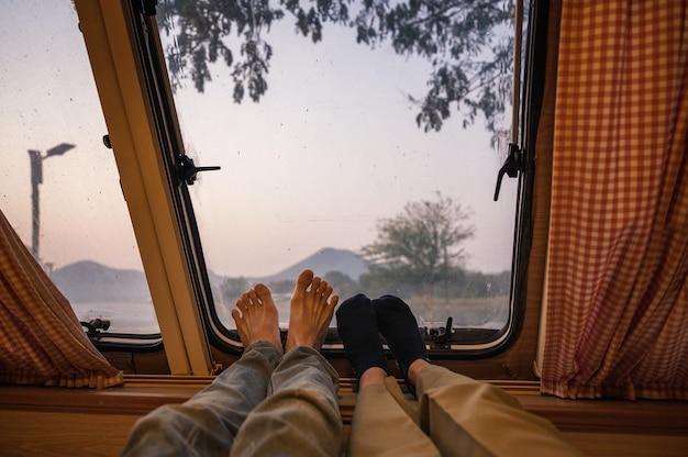 Gambe della giovane coppia rilassante in camper con vista sulle montagne in riva al lago al mattino