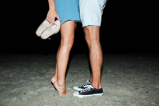 Gambe di giovane coppia in piedi sulla spiaggia di notte