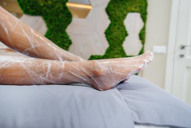 Gambe di un primo piano di giovane ragazza durante una procedura cosmetica in un moderno salone di bellezza. trattamenti termali presso il salone di bellezza.