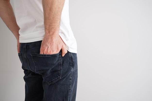 Gambe di un giovane uomo in jeans su sfondo grigio, spazio per il testo.
