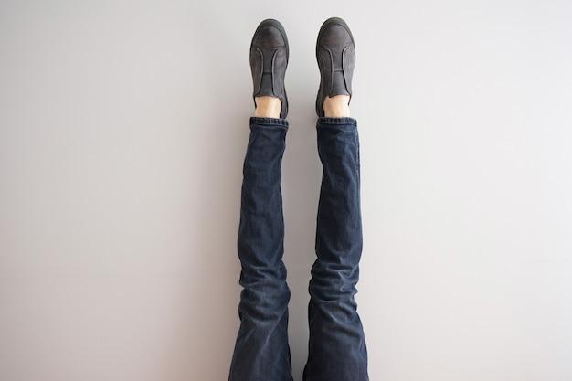 Gambe di un giovane uomo in jeans e scarpe su sfondo grigio.