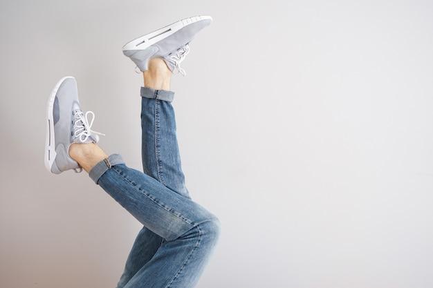 Gambe di un giovane uomo in jeans e scarpe da ginnastica su sfondo grigio.