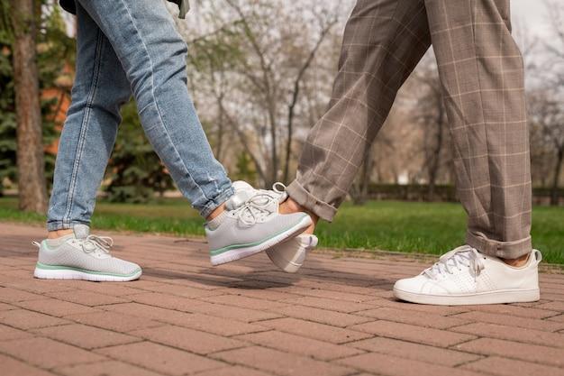 Gambe di giovane uomo e donna in pantaloni e scarpe sportive che fanno urto del piede sulla strada nel parco pubblico