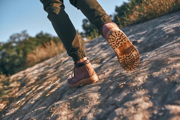 Gambe di un giovane blogger turistico che cammina in montagna foto ritagliata