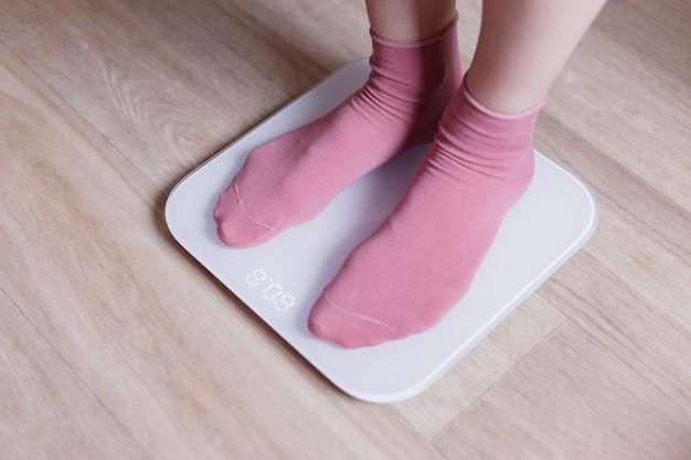 Gambe di una giovane donna che misura il suo peso su una bilancia intelligente moderna.