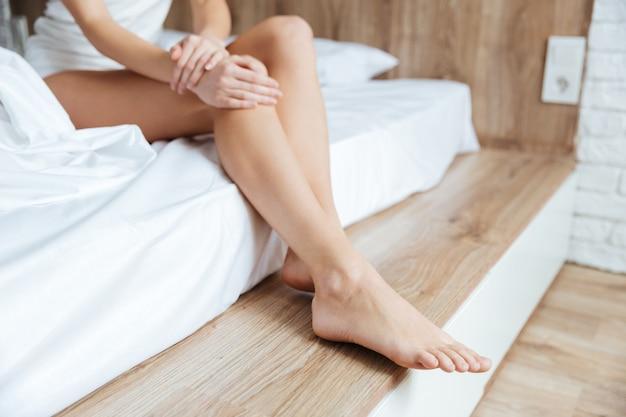 Gambe della giovane donna che si siede sul letto in camera da letto