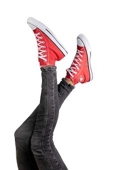Gambe di una giovane donna in eleganti scarpe da ginnastica rosse su superficie bianca.
