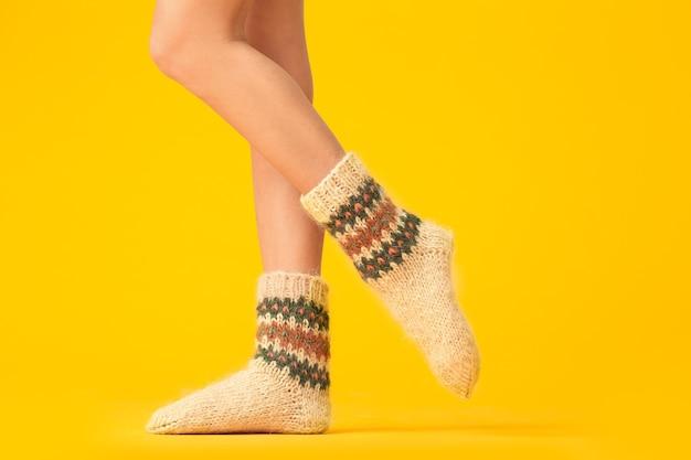 Gambe di giovane donna in calzini lavorati a maglia caldi sulla superficie di colore