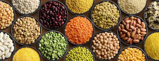 Fondo dei legumi e dei cereali: piselli, lenticchie, ceci del miglio dei fagioli in ciotole di legno nere. vista dall'alto.