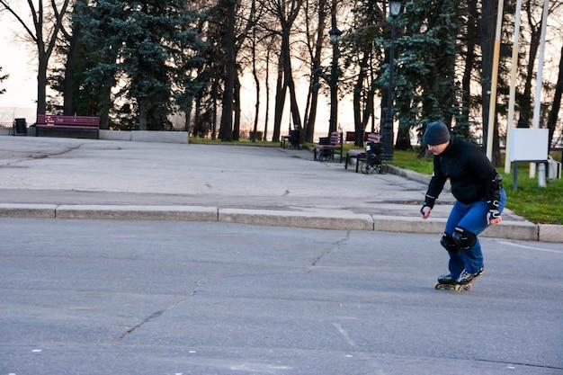 Attività di svago uomo pattinaggio a rotelle nel centro della città al tramonto. inverno. pattinaggio su strada.