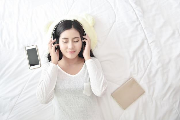 Tempo libero allegro benessere donna concetto. felice donna adolescente ascoltando musica indossare le cuffie dallo smartphone