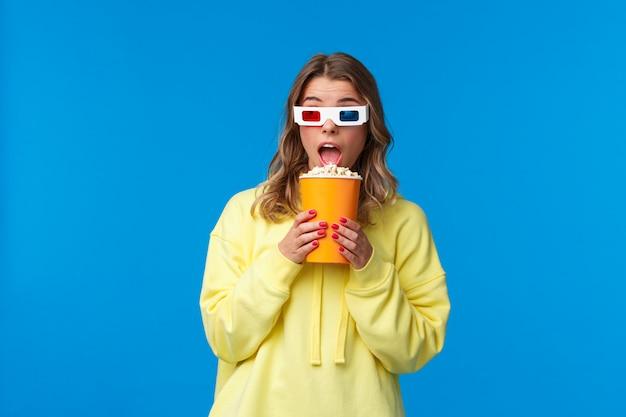 Concetto di svago, divertimento e gioventù. la giovane donna abbastanza bionda allegra in felpa con cappuccio gialla che mangia il popcorn distoglie lo sguardo e indossa gli occhiali 3d come guardare film nel cinema,