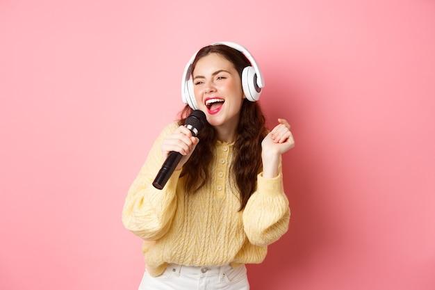 Tempo libero e stile di vita felice ragazza bruna divertendosi cantando karaoke in cuffie tenendo il microfono e fissando da parte lo schermo in piedi sopra la parete rosa