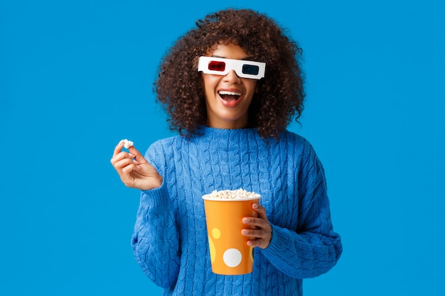 Concetto di tempo libero, stile di vita e persone moderne. spensierata rilassata e gioiosa, sorridente donna afro-americana con acconciatura afro, mangiare popcorn al cinema, indossare occhiali 3d e guardare film sorridente