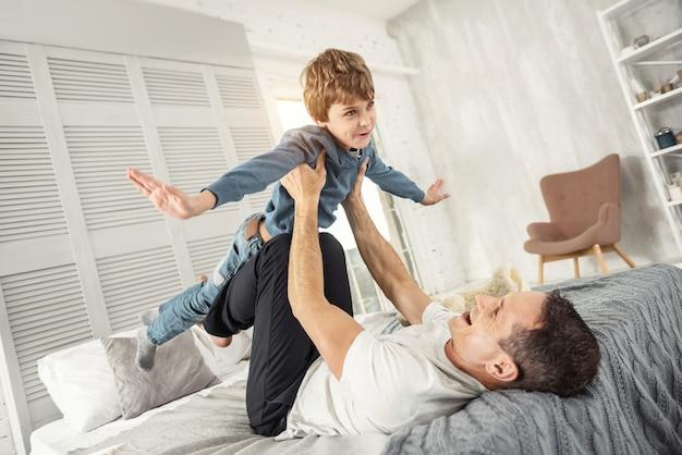 Tempo libero. bel ragazzo biondo contenuto che sorride e si diverte con il suo papà mentre è sdraiato sulla schiena sul divano