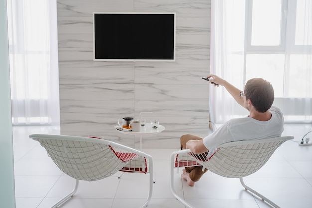 Tempo libero. uomo seduto su una sedia che guarda la tv con il telecomando in mano