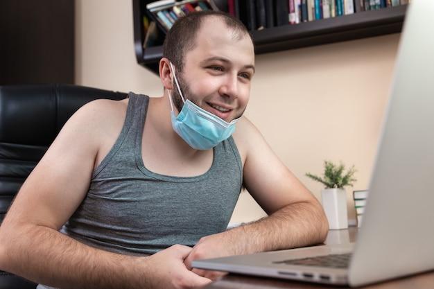 Tempo libero utilizzando laptop. un giovane ragazzo barbuto con maschera facciale in abiti da casa utilizza il laptop