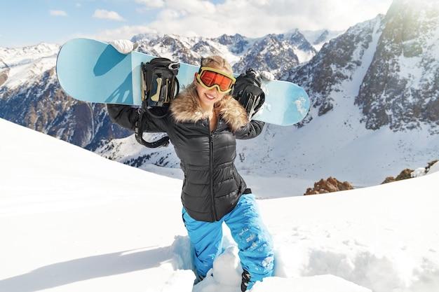 Tempo libero, sport invernali e concetto di persone - giovane donna felice con lo snowboard blu all'aperto.