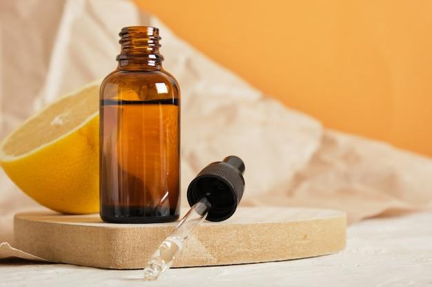 Limone e bottiglia di vetro marrone con contagocce per siero o olio cosmetico su un podio in legno a forma di cuore, concetto di cura del corpo ecologico