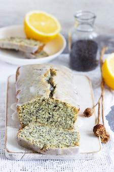 Torta al limone con semi di papavero, ricoperta di glassa su fondo chiaro. messa a fuoco selettiva.