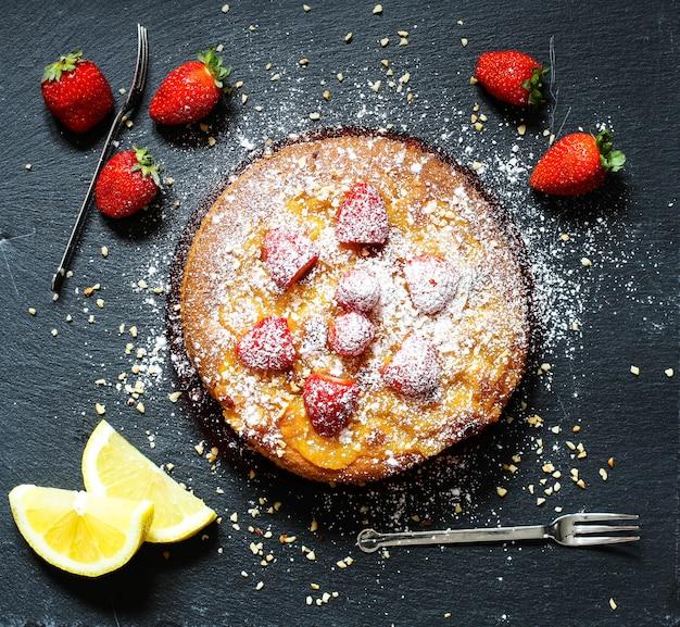 Torta al limone con fragole, zucchero fine cioccolato