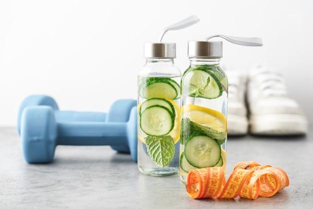 Acqua di limone, cetriolo e menta in bottiglie di vetro. acqua sfacciata per la disintossicazione o la dieta con manubri fitness in sottofondo