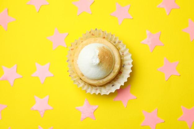 Cupcake al limone e stelle rosa su sfondo giallo