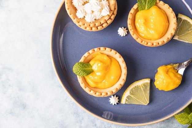 Mini crostate al lemon curd decorate con menta e fettine di limone su piatto in ceramica blu