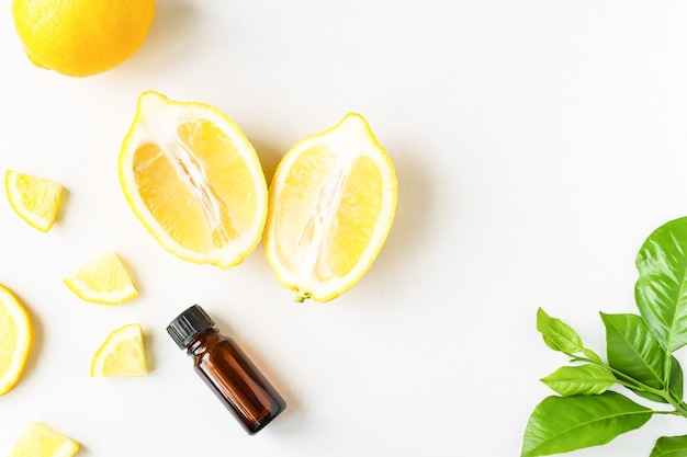 Olio essenziale di limone in una bottiglia d'ambra su un piatto bianco con fette di frutta e foglie verdi
