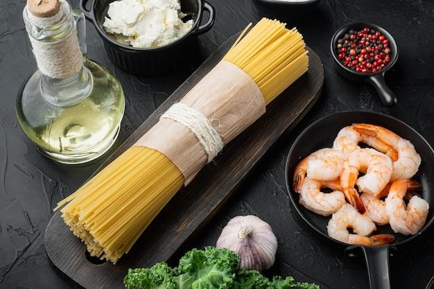 Gamberetti al formaggio con aglio e limone con set di ricette classiche con ingredienti per spaghetti, su sfondo nero