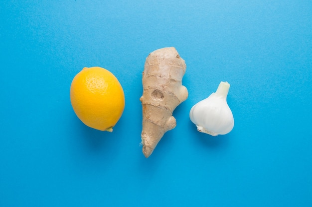 Zenzero di aglio limone su sfondo blu. la difesa naturale del corpo contro le malattie.