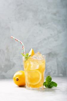 Tè freddo al limone su sfondo grigio cemento con menta e ghiaccio