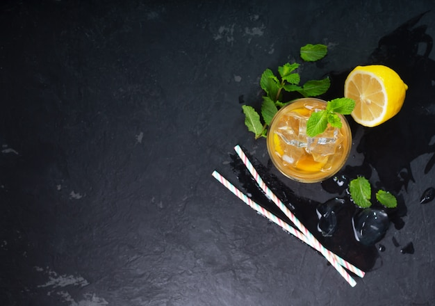 Tè freddo al limone su sfondo scuro con menta e ghiaccio, ез мшуц