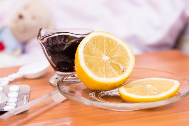 Limone, marmellata e pillole sul tavolo sullo sfondo di un letto per bambini con un peluche