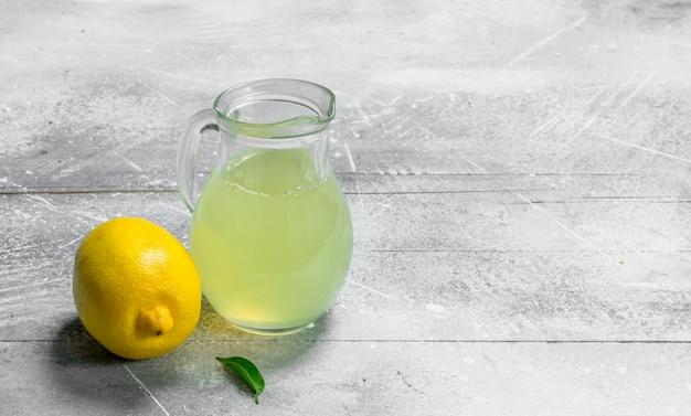Succo di limone nella brocca sul tavolo rustico.