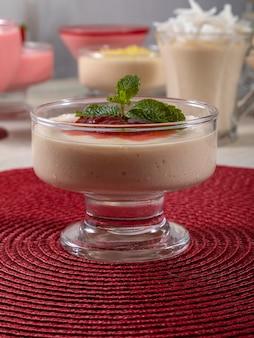 Mousse al limone in coppa di cristallo con topping di gelatina di fragole e menta.
