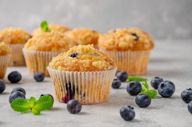Muffin al limone con mirtilli e shtreisel con frutti di bosco freschi su uno sfondo grigio cemento.