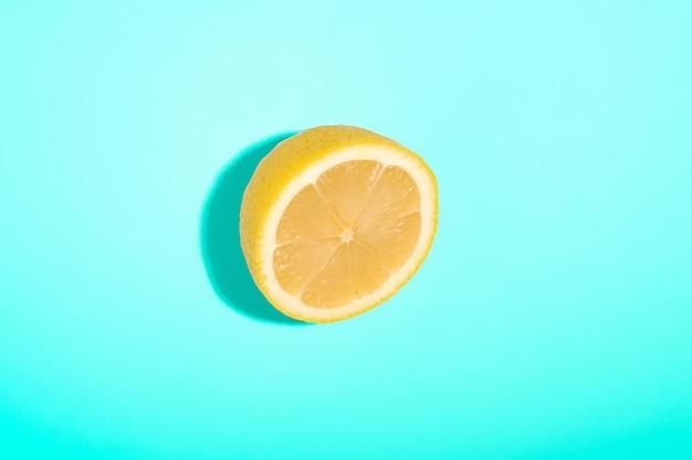 Limone affettato isolato sul minimo blu