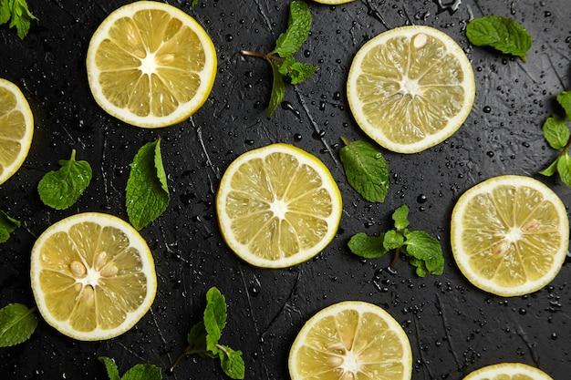 Fette di limone e foglie di menta fresca su sfondo nero con gocce d'acqua, laici piatta