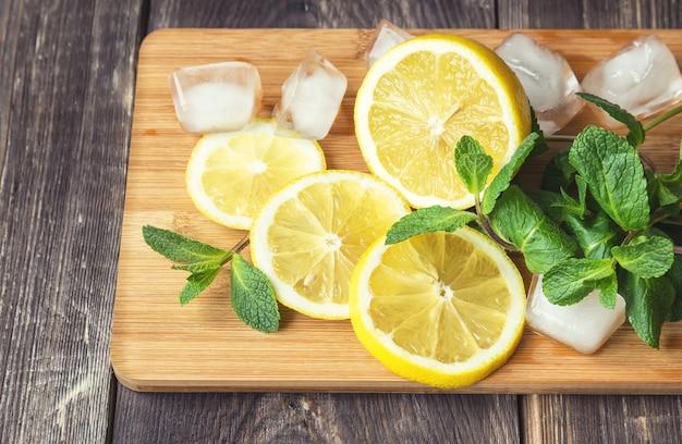 Fette di limone, foglie di menta e cubetti di ghiaccio sul tagliere
