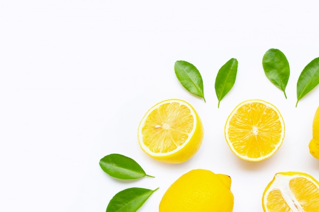 Limone e fette con le foglie isolate su fondo bianco.